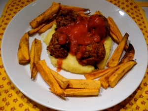 Meatballs, on top of creamy polenta, topped with sauce, and surrounded by SP fries